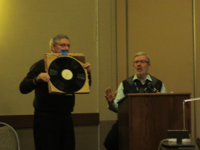 Gerry Orlando showing an original Vitaphone Disk being auctioned by Auction Host Leonard Maltin